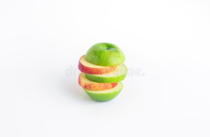 Mélange orange et vert de tranche de pomme sur le fond blanc de couleur photographie stock libre de droits