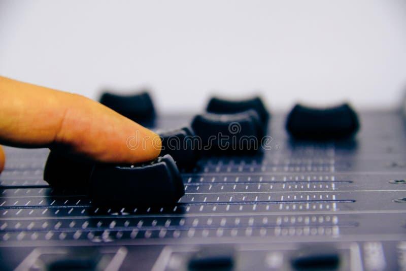 Mélangeur audio, contrôles de mélange de bureau et affaiblisseur, console de mélange de musique avec la main du technicien déplaç image stock