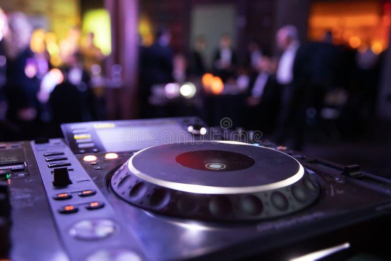 Mélangeur de console du DJ à une boîte de nuit La disco, banquet, danse de fond brouillée par gens image stock