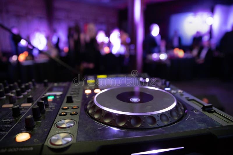 Mélangeur de console du DJ à une boîte de nuit La disco, banquet, danse de fond brouillée par gens photographie stock libre de droits