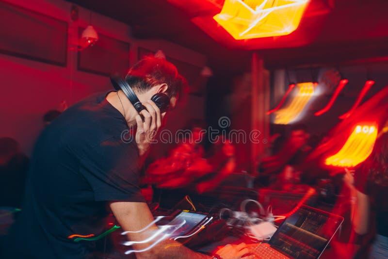 Mélangeur du DJ dans une boîte de nuit avec les lignes continues abstraites en mouvement de mouvement lumières colorées rougeoyan photos stock