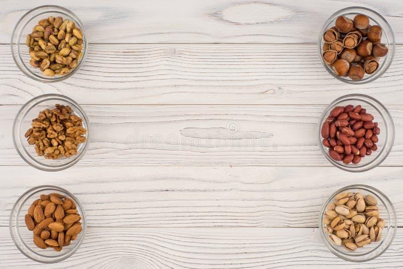 Mélangez les écrous dans un bol en verre sur la vieille table en bois image libre de droits