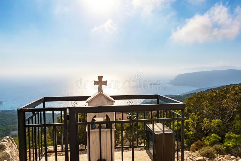 Mémorial de bord de la route avec la croix sur la colline au-dessus de la baie Rhodes, Grèce de mer Égée images stock