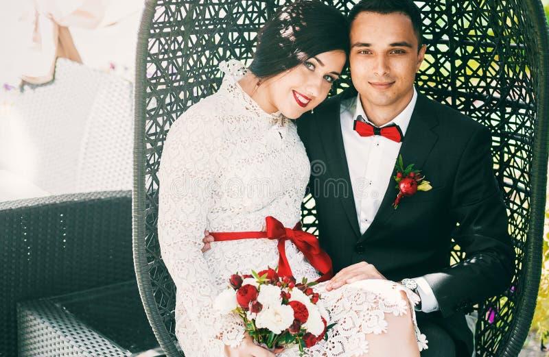 Ménages mariés heureux dans la chaise de canne noire photographie stock libre de droits