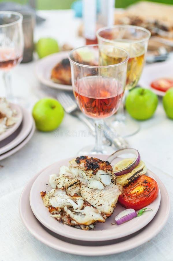 Mérou grillé, verres avec du vin blanc et rosé, plats, légumes, salade et fruits sur la table Partie d'été dans l'arrière-cour image libre de droits