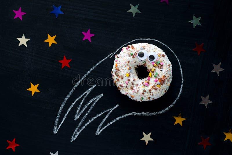météorite de beignet avec parmi les étoiles sur un fond noir de tableau, le divertissement des enfants drôles avec la nourriture, images libres de droits