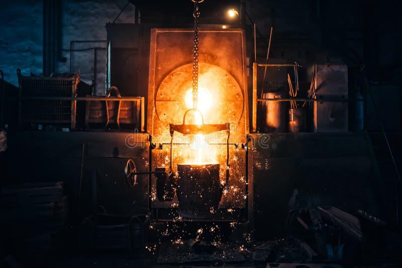 Métal de fonte à une centrale métallurgique Fer liquide de la poche en métal versant dans les bâtis à l'usine photographie stock