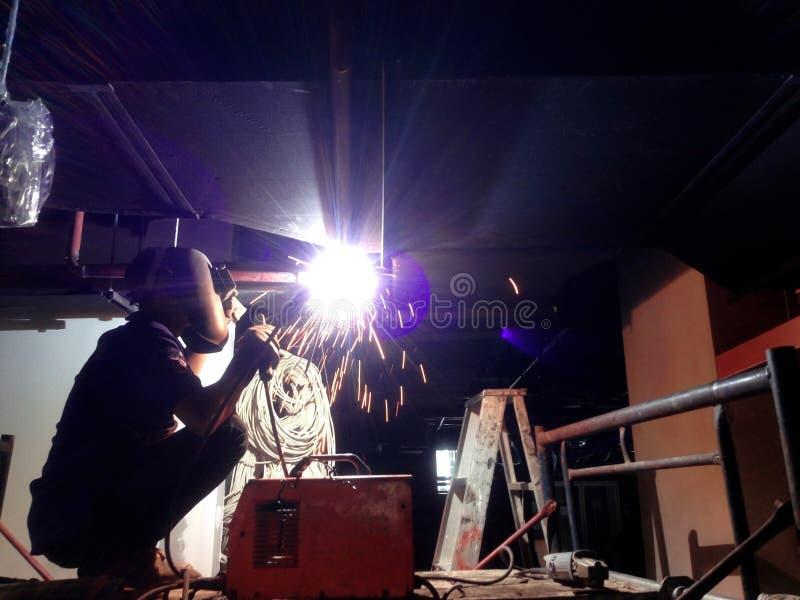 Métal de soudure de soudeuse dans le chantier de construction et employer le masque de soudure image stock