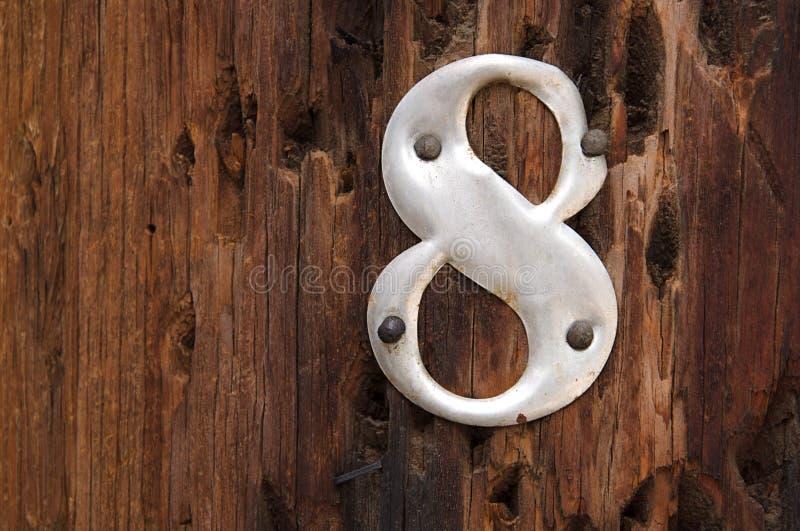Métal numéro 8 sur le fond en bois photos stock