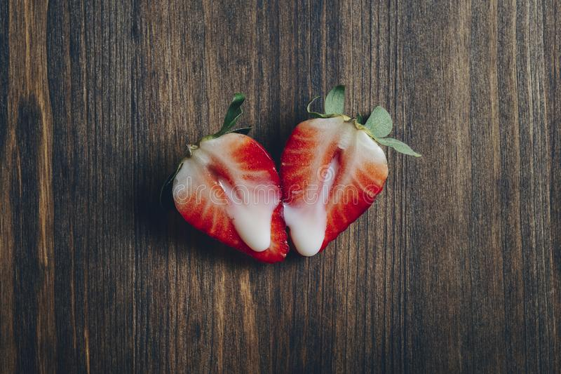 Métaphore de sexe avec des fraises sur la table en bois photo stock