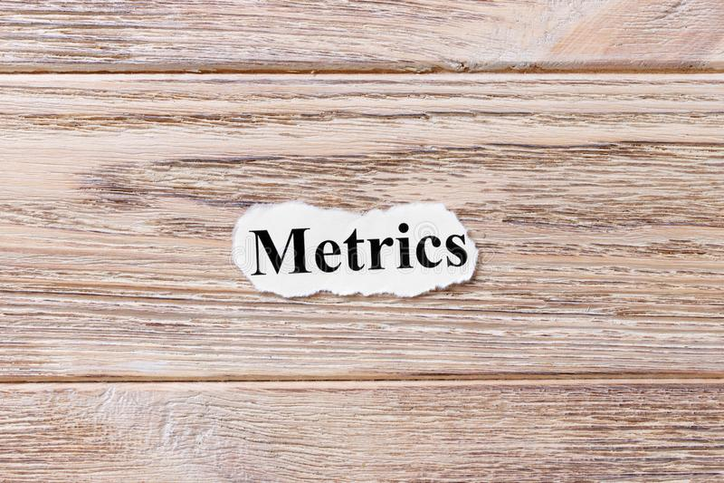 Métrique du mot sur le papier Concept Mots de la métrique sur un fond en bois images stock