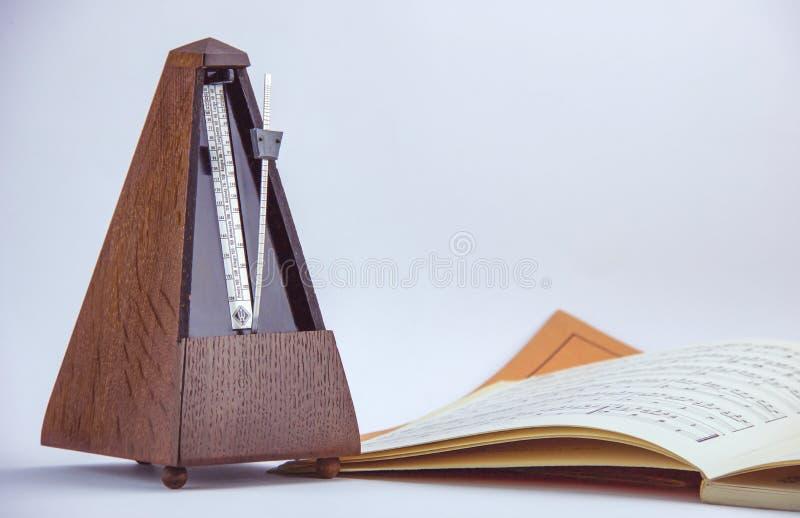 Métronome en bois de vieux cru près d'une feuille de musique photographie stock