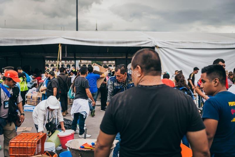 MÉXICO - 20 DE SEPTIEMBRE: La gente que se ofrece voluntariamente en una colección se centra para recolectar disposiciones y las  imágenes de archivo libres de regalías