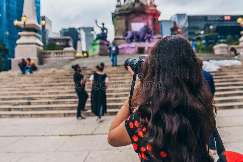 MÉXICO - 20 DE SEPTIEMBRE: Turista que toma imágenes en la plaza de la independencia Angel Monument imagen de archivo