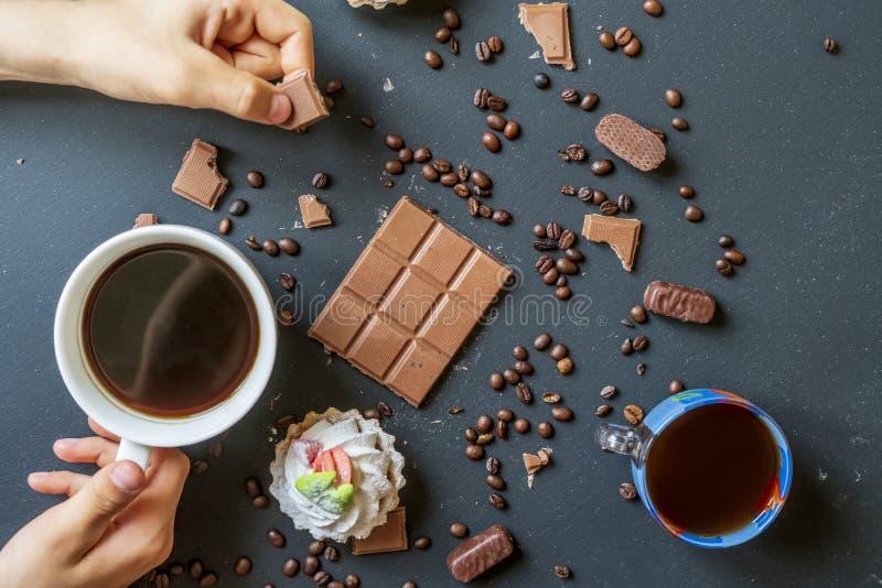 Même le café avec des bonbons et des biscuits sur la table foncée f photographie stock libre de droits