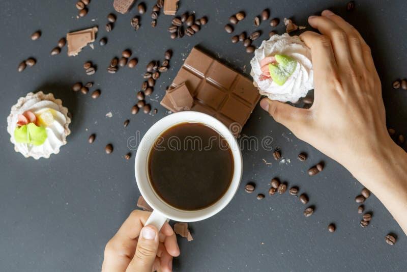 Même le café avec des bonbons et des biscuits sur la table foncée f photo stock