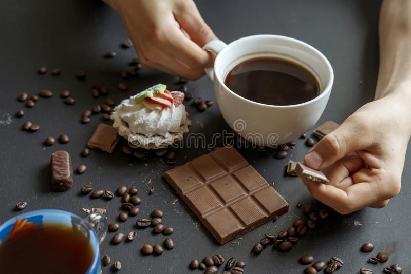 Même le café avec des bonbons et des biscuits sur la table foncée f image libre de droits