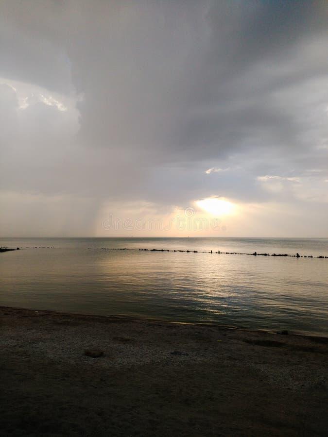 Même le coucher du soleil sur la mer dans la perspective de l'avant de pluie approchant photo stock