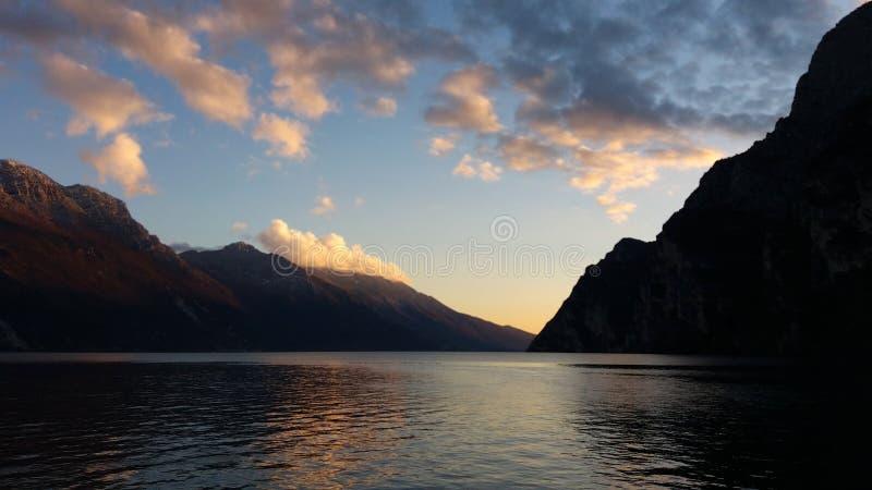 Même le paysage du lac de montagne, nuages roses éclairés à contre-jour par le coucher de soleil photo stock
