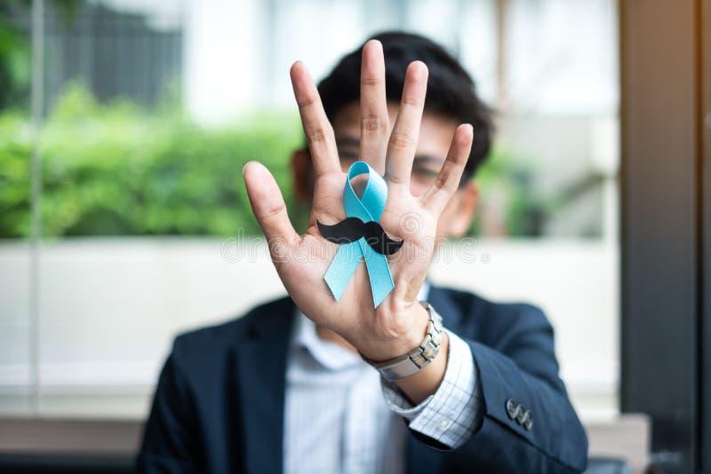 Mês da conscientização do câncer da próstata, homem de negócio que guarda a luz - fita azul com o bigode para a vida e a doença d imagens de stock royalty free