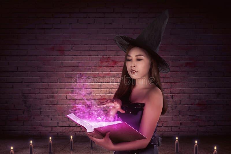 Místico de uma mulher asiática bonita da bruxa com um livro mágico fotos de stock