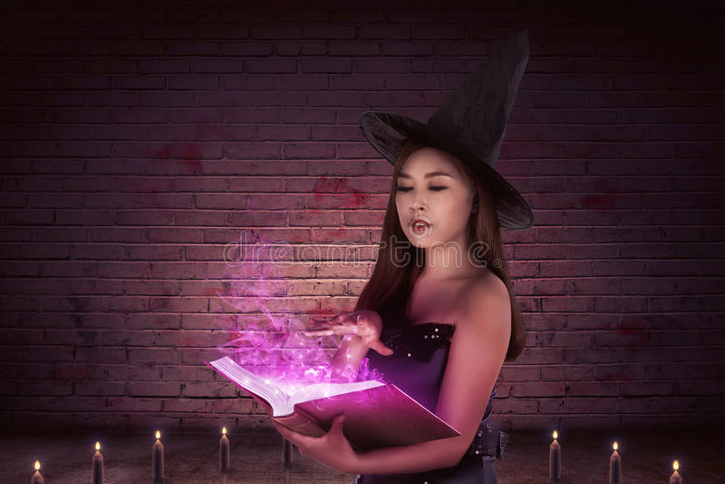 Místico de una mujer asiática hermosa de la bruja con un libro mágico fotos de archivo