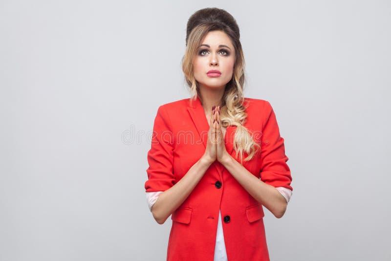 Mój bóg zadawala wybacza ja Występować z prośbą pięknej biznesowej damy z fryzurą i makeup w czerwieni fantazji blezerze, stoi z  obraz royalty free