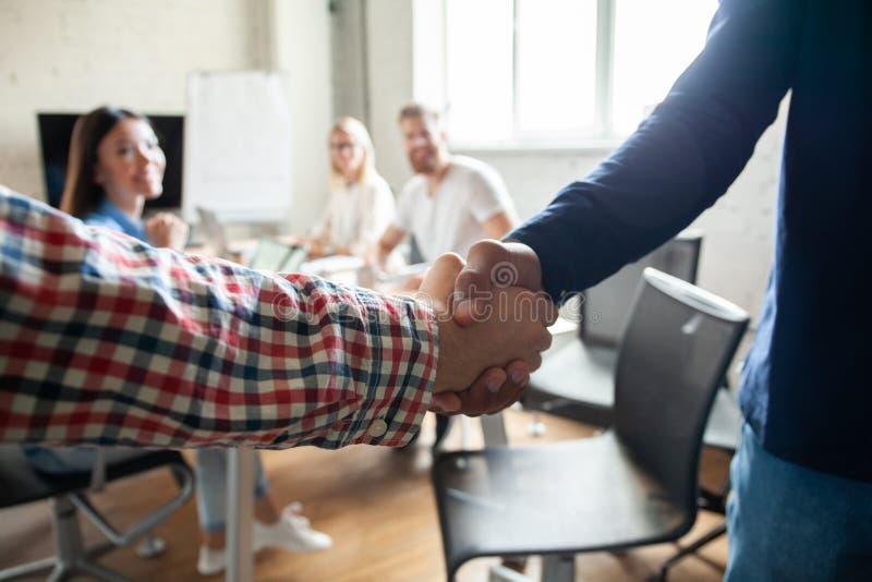 Mój gratulacje! Dwa rozochoconego biznesmena trząść ręki podczas gdy być w biurze wraz z ich kolegami zdjęcia stock