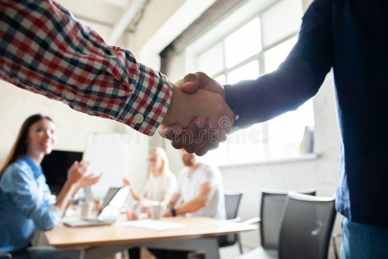 Mój gratulacje! Dwa rozochoconego biznesmena trząść ręki podczas gdy być w biurze wraz z ich kolegami obrazy royalty free