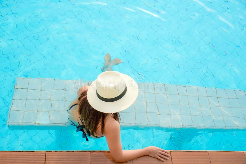 mój pracy widzią wakacje pracy Styl życia kobieta szczęśliwa z bikini i dużym kapeluszowym relaksować na pływackim basenie, zdjęcia stock