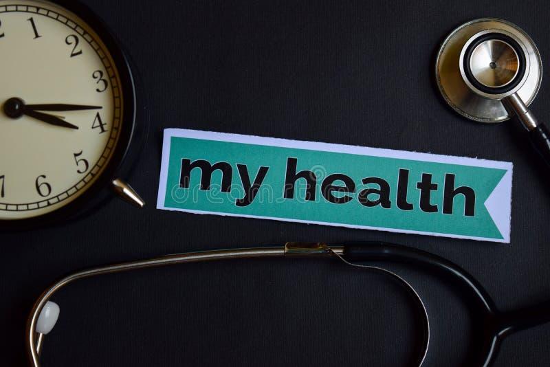 Mój zdrowie na druku tapetują z opieki zdrowotnej pojęcia inspiracją budzik, Czarny stetoskop zdjęcie stock