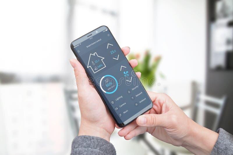 Móvil moderno app del uso de la mujer con el interfaz plano moderno del diseño para controlar seguridad en el hogar, la iluminaci fotos de archivo libres de regalías