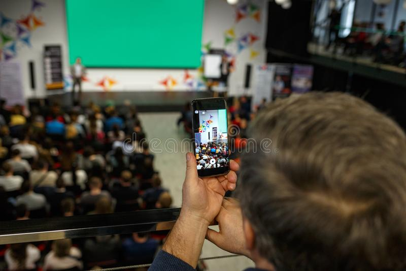 Mówca przy Biznesową konferencją i prezentacją Widownia przy sala konferencyjną Mężczyzna utrzymuje rejestr na smartphone zdjęcie stock