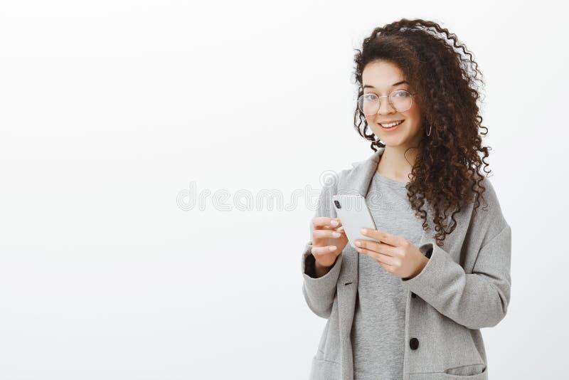 Mówi ja twój numer telefonu Portret elegancka atrakcyjna ufna kobieta w modnych szkłach i siwieje żakiet, trzyma zdjęcia stock