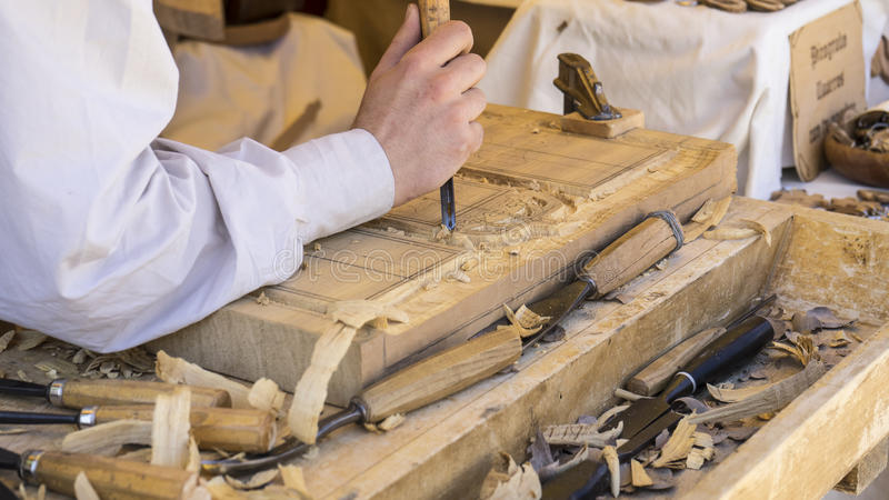 Möbel, Handwerker, der Holz in einer mittelalterlichen Messe, Zimmerei schnitzt lizenzfreie stockfotos