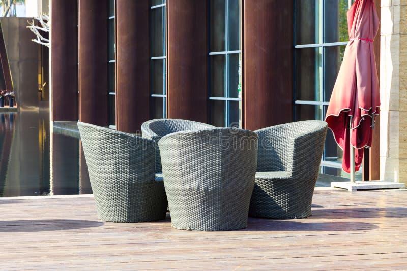 Möbel im Freien: Eine Gruppe Rattansessel auf Terrasse lizenzfreies stockfoto