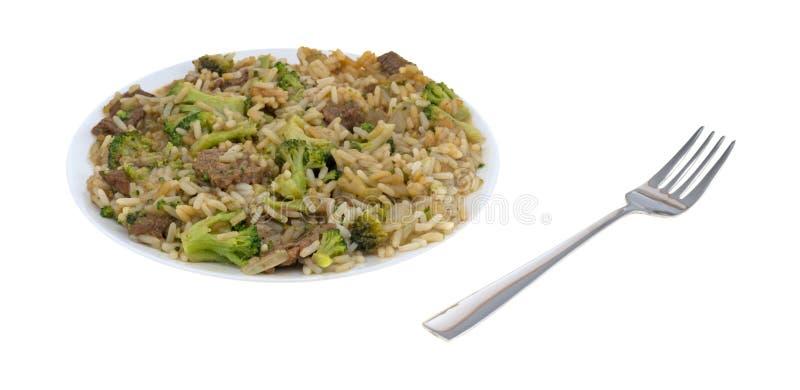 Möbeln Sie Brokkoli- und Reisabendessen auf einer Platte mit Gabel auf lizenzfreies stockfoto