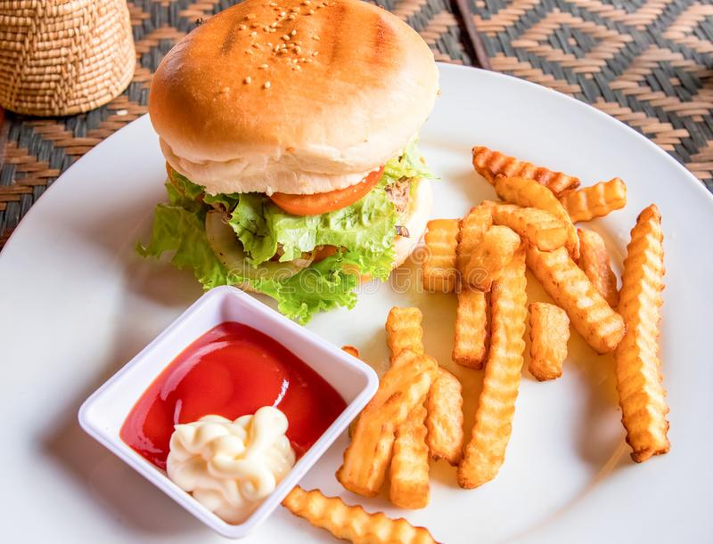Möbeln Sie Burger mit Pommes-Frites, Ketschup und Majonäse auf weißer Platte auf Reiches nutrititive Frühstück stockbild