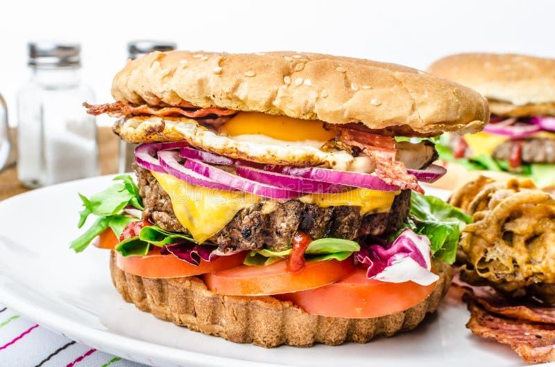 Möbeln Sie Burger, rote Zwiebel und Spiegelei auf stockfotos