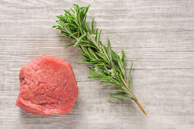Möbeln Sie Fleisch und Rosmarin auf weißem Holz oder Steinhintergrund auf stockbild
