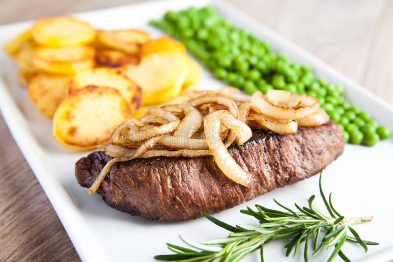 Möbeln Sie Leiste mit gebratenen Kartoffeln, Zwiebeln und grünen Erbsen auf lizenzfreie stockfotos