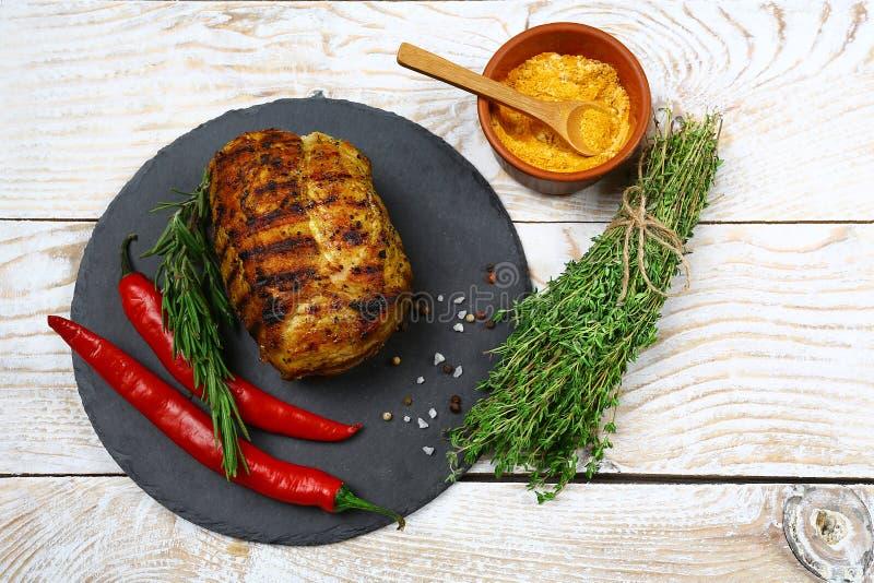 Möbeln Sie Steak auf einem runden Schieferbrett mit Peperonipaprikas, -kräutern und -gewürzen auf Auf hölzernem Brett Menürestaur stockbilder