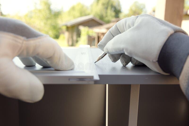 Möbelversammlung Arbeitskraft in den Schutzhandschuhen, die Teil des Küchenschranks mit Baumachthaber messen stockfoto