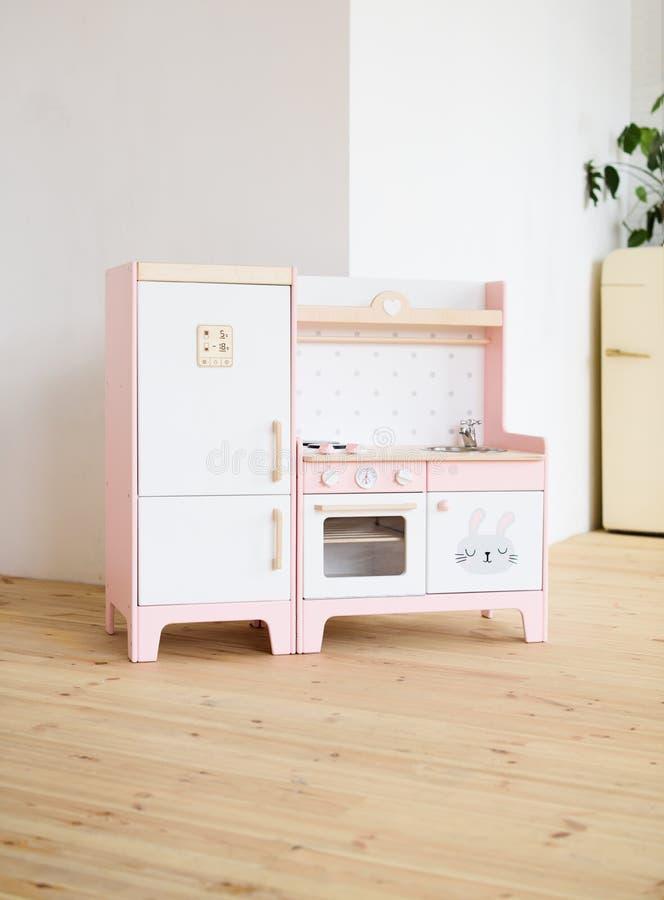 Möblemang för barn Sött litet rosa kök med kylen, ugnen, ugnen och vasken i ljust rum arkivbilder