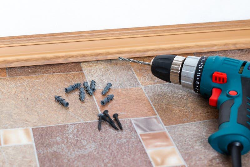 Möblemangenheten särar och hjälpmedel för självenhetsmöblemang, på golvet Installation av den plast- golvsockeln detaljinterior fotografering för bildbyråer