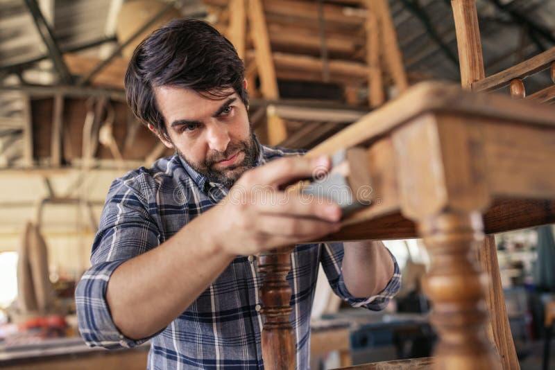 Möblemangtillverkare som sandpapprar en stol i hans snickeristudio arkivfoto