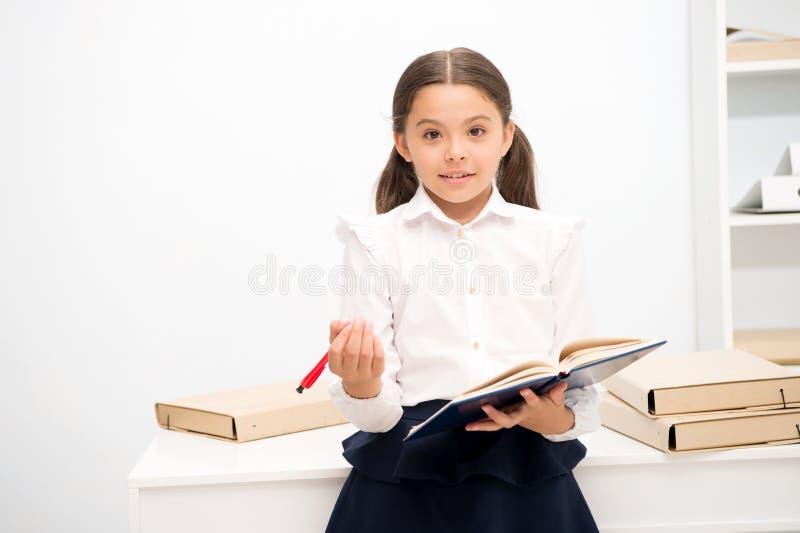 Möchten neues Schulprogramm anwenden Mädchen hält den Auflagenstift, der Freiwillige sucht Das Schulmädchenstudieren umfassen soz stockbild
