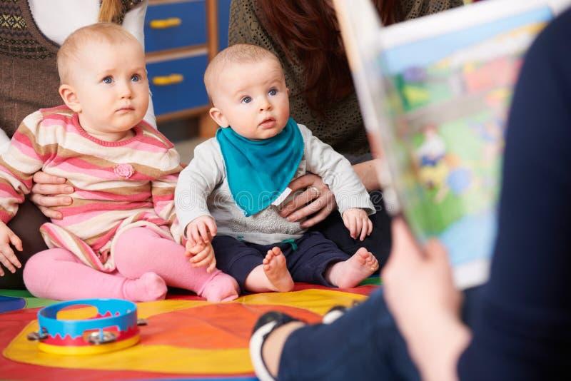 Mödrar med barn på behandla som ett barn gruppen som lyssnar till berättelsen royaltyfri fotografi