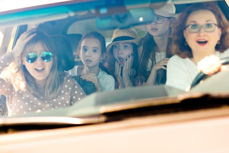 Mödrar med döttrar som skrämdes i bil- se, förbluffade vid inkommande olycka royaltyfria foton