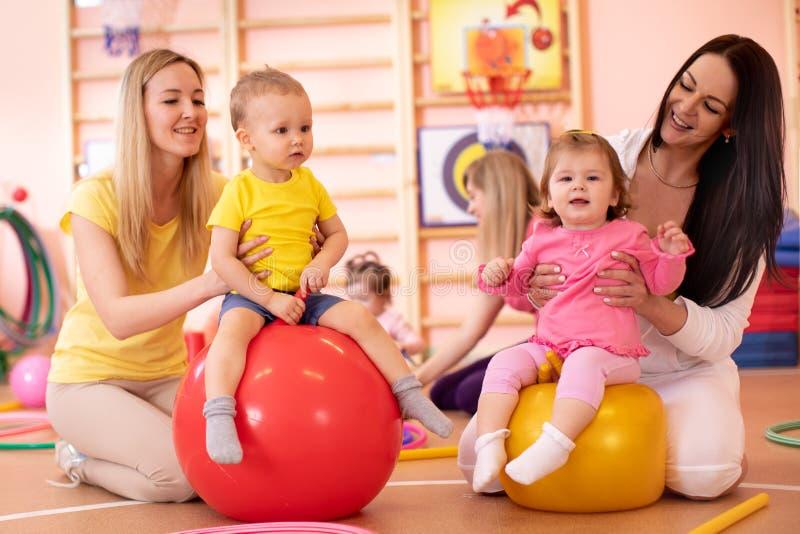 Mödrar med lyckligt behandla som ett barn göra övningar med den gymnastiska bollen i idrottshall Begrepp av att att bry sig för h royaltyfri fotografi